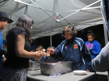 Students from the Clontarf Academy serving stew to community garden visitors for Will Stevens' guided tour